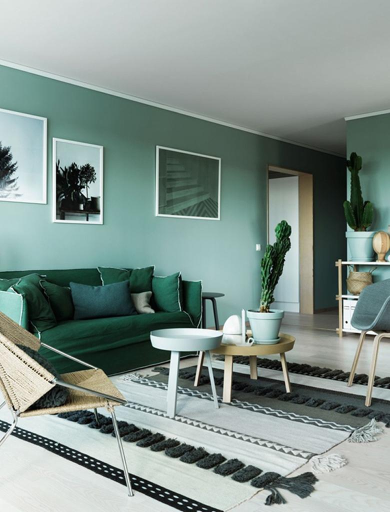 ciemnozielona sofa na tle zielonej ściany